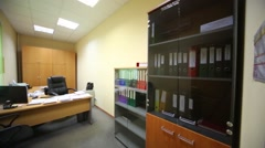 A small office with spacious work desk and bookcase with folders Stock Footage