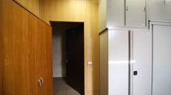 Small office room with a few tables and a gray office cabinets Stock Footage