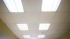 Light office ceiling with a row lamps switched off and on - stock footage