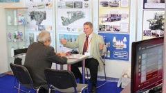 Two men sitting at table and talk at International Exhibition Stock Footage