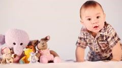 Little boy crawling forward near the pile of toys in the studio Stock Footage