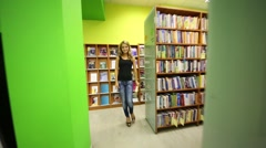 Beautiful girl closes the book and walks along the bookshelves Stock Footage