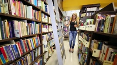Young girl climbs the ladder and put the book on the top shelf Stock Footage