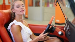 Young beautiful girl sitting at the wheel of the car Stock Footage