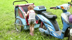Little girl and boy play at trailer attached to e-scooter Stock Footage