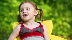Little girl tells about herself, sitting on chair at green lawn. - stock footage