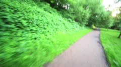 Pathway in park, shot from jolting scooter moving along it. - stock footage