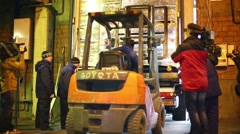 Press representatives shoot loader lifts pallet at doors of truck Stock Footage
