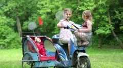 Children play sitting on scooter at green grassy lawn. Stock Footage