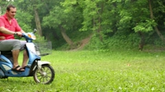 Man on scooter with trailer stops at green grassy lawn. Stock Footage