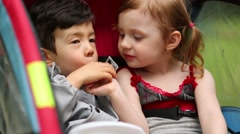 Little boy and girl eat potato chips, sitting in trailer. Stock Footage