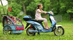 Three children play sitting in trailer and on scooter. Stock Footage