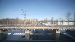 View from window of train moving over frozen river by bridge. Stock Footage
