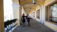 Mother and daughter walk along open gallery with showcases. Stock Footage