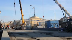 Workers move freights with cranes during repairing Palace bridge Stock Footage