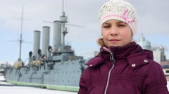 Little girl stands against the cruiser Aurora at embankment Stock Footage