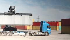 Container Handler unloading a Truck in Port Terminal. No Logos. Stock Footage
