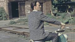 East Germany 1960's: man riding a IWL Troll scooter Stock Footage