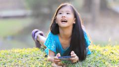 Little Asian child playing game on smart phone in the park Stock Footage