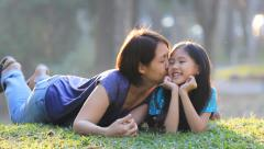 Asian mother kisses her daughter on grass at sunny summer day in park Stock Footage