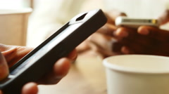 Close up of a couple playing with their phones while on a date at a cafe and Stock Footage