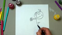 The man draws a marker humorous picture - stock footage