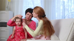 Grandmother and mother combed the little girl. Stock Footage