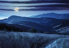 path on hillside meadow in mountain at night - stock photo