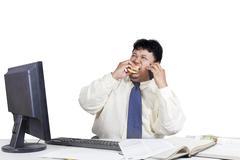 entrepreneur eating burger while working - stock photo
