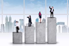 Entrepreneurs standing on business graph Stock Photos