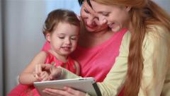 Grandmother and mother fun teaching little girl to use the touchpad. - stock footage