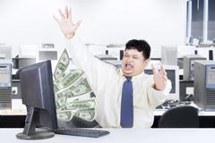 male worker with money from computer - stock photo