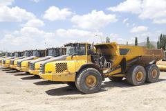 Yellow heavy construction tipper trucks Stock Photos