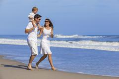 Happy man woman child family playing on beach Stock Photos