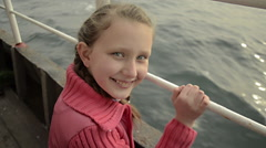 Teenage ponytail blonde pink jacket girl, smiling,  banister, on boat voyage Stock Footage