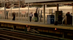 People getting off train wide still shot walking with bags to station travelers Stock Footage