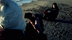 Female director shooting with model on the beach Stock Footage