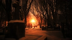Light snow falling in a creepy cemetery with red glowing light, Reykjavik - stock footage