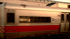 Commuter train goes by right to left away from camera pans, see electrical grid. Stock Footage