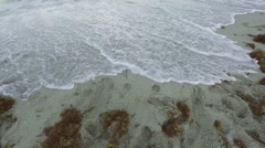 The word Summer being washed away by the tide on a beach - stock footage
