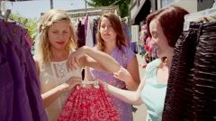 Three women shopping for clothes at an outdoor market Stock Footage