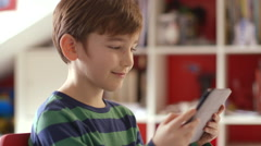 Stock Video Footage of Young boy playing games on a touchscreen tablet