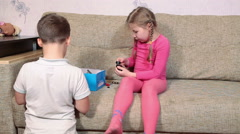 Kids six and seven years old playing with toys on sofa at home Stock Footage