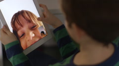 Young boy video chats with his sister on a tablet Stock Footage