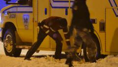 Paramedic with tuque shoveling snow under ambulance wheel - stock footage