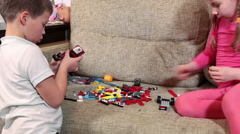 Close-up view of two preschool kids playing with a constructor on sofa Stock Footage