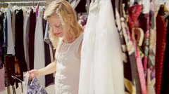 Woman shopping for clothes at an outdoor market Stock Footage