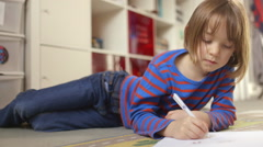 Happy little girl busy drawing with coloured pencil - stock footage