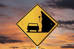 falling rocks warning sign with sunrise - stock photo
