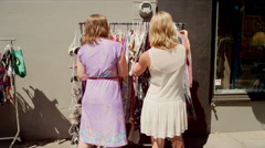 Two women shopping for clothes at an outdoor market Stock Footage
